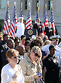 A woman wipes tears as she listens to the national anthem as  Chairman of the Joint Chiefs of Staff Admiral Mike Mullen, left, United States President Barack Obama, center, and U.S. Secretary of Defense Robert Gates, right, stand in the background during an event to mark the anniversary of the 9/11 terrorist attacks at the Pentagon Memorial, Saturday, September 11, 2010 in Arlington, Virginia. Obama delivered remarks, laid a wreath, and greeted with victims' families during the event on the 9th anniversary of the tragedy. .Credit: Alex Wong - Pool via CNP