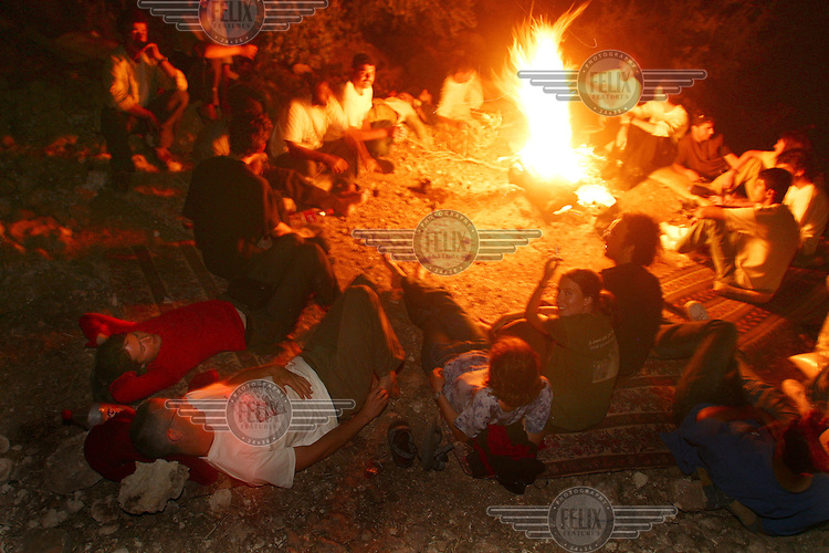 ISM activists join Israeli peace activists by the campfire at Mas'ha camp. The camp is on Palestinian land confiscated by the Israeli government to build a separation wall.