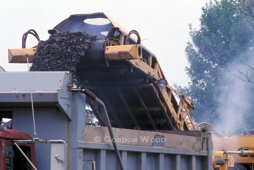 Asphalt Debris Ejected from Pavement Profiler onto Dump Truck during Road Preparation