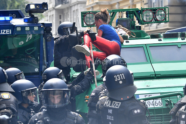 A female protestor climbs onto an armoured police vehicle during demonstrations against the G20 summit in Hamburg, Germany, 7 July 2017. The summit, a meeting of the governments of the twenty largest world economies, begins on the 7 July and concludes on the 8 July. Photo: Boris Roessler/dpa /MediaPunch ***FOR USA ONLY***