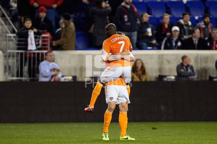 Omar Cummings (7) of the Houston Dynamo celebrates with Cam Weaver (15) after defeating the New York Red Bulls. The Houston Dynamo defeated the New York Red Bulls 2-1 (4-3 on aggregate) in overtime of the second leg of the Major League Soccer (MLS) Eastern Conference Semifinals at Red Bull Arena in Harrison, NJ, on November 6, 2013.