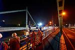 NIEUWEGEIN -  In het holst van de nacht heeft Rijkswaterstaat door Civiele Technieken deBoer – Spanlift een tijdelijke hulpbrug vanaf een ponton op de plaats van de weggeschoven Jutphasebrug over het Amsterdam-Rijnkanaal getakeld. De uit 1936 daterende boogbrug krijgt door bouwcombinatie KWS-Mercon een opknapbeurt en is een avond eerder op hoge hulppijlers verschoven waar later de stalen constructie versterkt, brugdek en pijlers gerepareerd en de brug opnieuw geverfd wordt. De Jutphasebrug zal naar een ontwerp van ingenieursbureau Movares volgend jaar 45 cm hoger worden teruggeschoven om hoger containervaart eronder mogelijk te maken. De renovatie van de Jutphasebrug is onderdeel van het project KARGO(Kunstwerken Amsterdam-Rijnkanaal Groot Onderhoud) waarbij acht stalen bruggen over het Amsterdam-Rijnkanaal, Lekkanaal en Buiten-IJ worden gerenoveerd en verhoogd. Op de achtergrond(links) is de ernaast liggende trambrug zichtbaar die destijds al op de juiste hoogte was gebouwd. COPYRIGHT TON BORSBOOM
