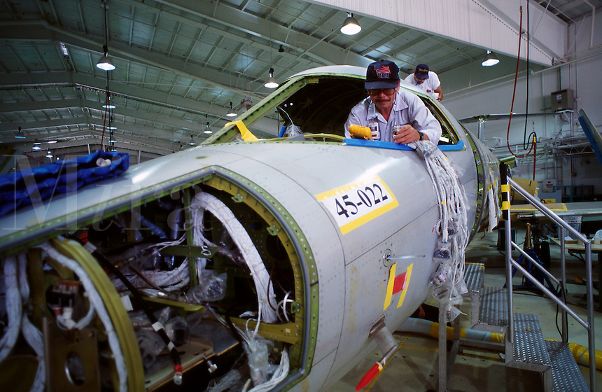 Workers assemble components of a business jet on an assembly line.