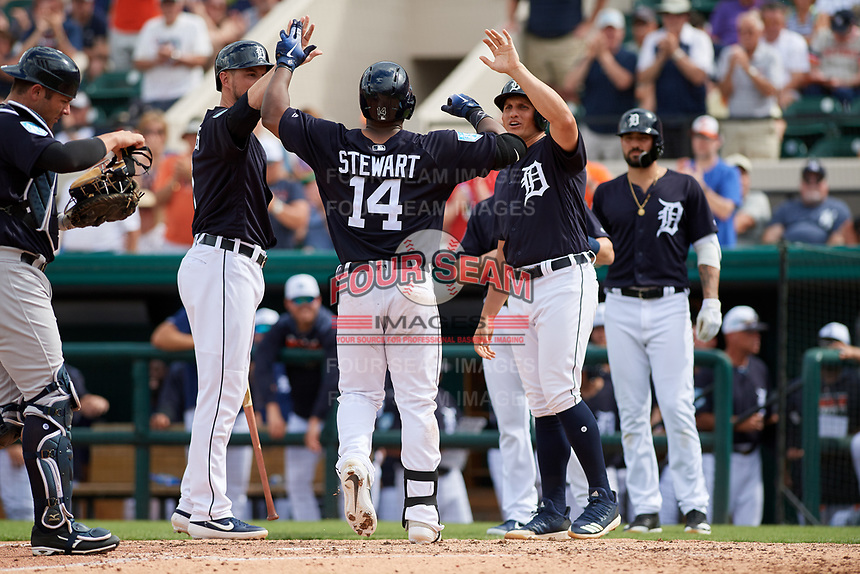 Detroit Tigers left fielder Christin Stewart (14) is congratulated by Jordy Mercer (left) and Mikie Mahtook (right) after hitting a home run during a Grapefruit League Spring Training game against the New York Yankees on February 27, 2019 at Publix Field at Joker Marchant Stadium in Lakeland, Florida.  Yankees defeated the Tigers 10-4 as the game was called after the sixth inning due to rain.  Nicholas Castellanos (background right) is also shown.  (Mike Janes/Four Seam Images)