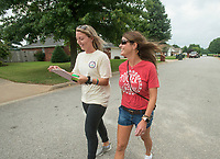 NWA Democrat-Gazette/BEN GOFF @NWABENGOFF<br /> Halston Shaw (left), a 4th grade teacher at Tucker Elementary, and Kim White, the school's library media specialist, walk door-to-door Wednesday, Aug. 8, 2018, in a neighborhood near the school in Rogers. Teachers and staff at the school split into groups to knock on the doors of the school's more than 600 students to personally invite their family to the meet and greet at the school Monday. Casey Wolfe, a kindergarten teacher at the school, helped organize the community walk after attending a Professional Learning Community seminar over the summer break. Wolfe hopes the effort will get more parents involved with the school.