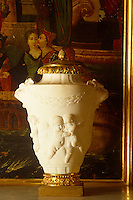 An alabaster urn with a gilt lid and base featuring dancing cherubs in relief