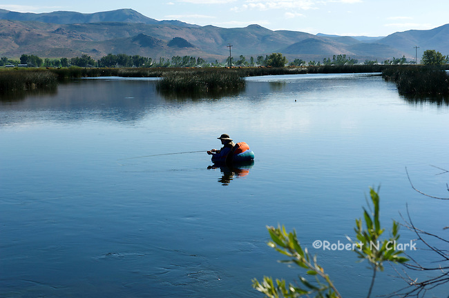 A fly fisherman in his float tube enjoys early morning fishing on Silver Creek