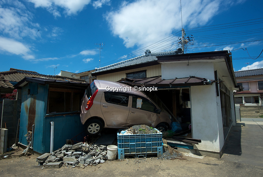 A car in the room of a house in Ishinomaki, that was devastated by the tsunami on 11th March 2011 photographed again 14th June 2011. The half smashed up town remains a mess of rotting fish and half demolished building where the residents are slowly begining to return..14 Jun 2011