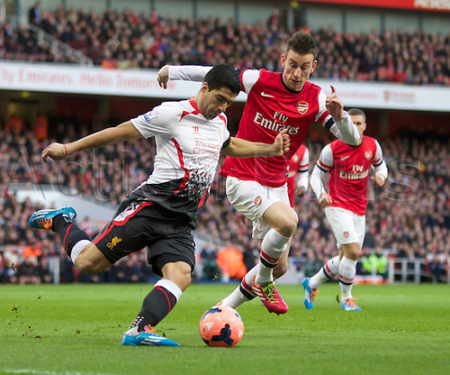 16.02.2014 London, England.  Luis Suárez of Liverpool (l) looks to clear the ball under pressure from Laurent Koscielny of Arsenal during the FA Cup 5th Round game between Arsenal and Liverpool from the Emirates Stadium.