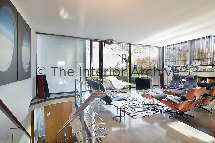An inspiring first floor living room. The spacious area is furnished with classic Eames chairs and a     white seat arranged in a square. The floor to ceiling windows allow plenty of light into the room.