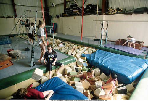 A group of young children practice their gymnastics in the foam pit at Sutton School, Surrey, 920615. Photo: Richard Francis/Action Plus...1992.teach teaching teacher teachers learn learning.coach coaching coaches.tuition tutor instructor instruction trainer child children.kids girl girls infant infants Youngster Youngsters boy boys.childrens sport gymnastic gymnast gymnasts.female.lesson learn learning