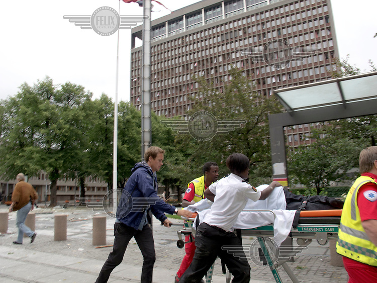 Oslo Norway 20110722 -  Terror attack on the government quarters in Oslo and AUF youth camp at Utoya / Utøya.  Pictured: injured person taklen away by paramedics in front of the the government building, housing among others the prime minister´s office (Regjeringsblokka), 18 minutes after the attack. Photo/copyright: Torbjorn Gronning.
