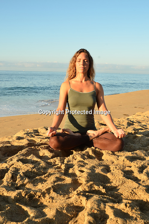 Stock photo of a woman doing yoga on the beach