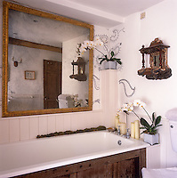A white country bathroom with painted tongue and groove panelling on the lower half of the walls. A gilt framed mirror hangs on the wall above the bath.