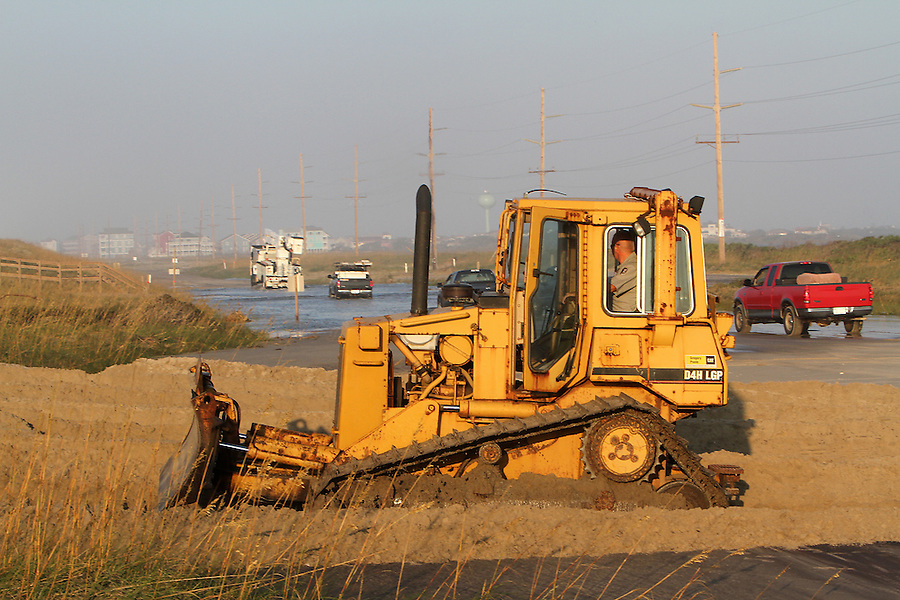 A road crew worker pushes sand off of N.C. 12, on Hatteras Island in North Carolina while an electric utility crew and other trucks drive through the flooded street toward Hatteras Village on Sunday, Aug. 28, 2011. Photo by Ted Richardson