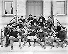 From the 1890s: Football Team on the steps of Science Hall (LaFortune Hall), 1897..Includes John Eggeman (upper center with white shoulder pads), Frank Hering (upper right with ND baseball hat), Captain Jack Mullen holding the football, and John Farley (second row, far right)..Image from the University of Notre Dame Archives.