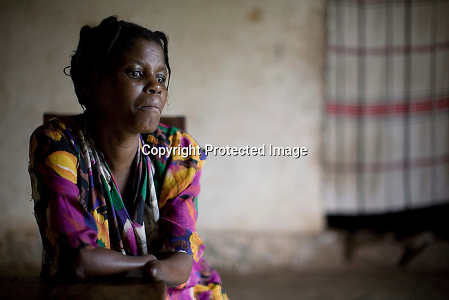 BUKAVU, DEMOCRATIC REPUBLIC OF CONGO - OCTOBER 29: Janette Vumilia, age 30, sits in her living room in her small house on October 29, 2007 Bukavu, DRC. Janette was abducted, held captive and raped by rebels in the DRC conflict. Her hands were amputated before she was finally released. Janette lives with her husband and four children, which is quite unusual, as many men abandon their wives or daughters if they have been raped. The DRC conflict has seen an unprecedented high rate of rape and sexual abuse of women. The culprits are both different rebel groups and government soldiers and very few are punished. About 27,000 sexual assaults were reported in South Kivu province alone in 2006, according to the United Nations. (Photo by Per-Anders Pettersson)