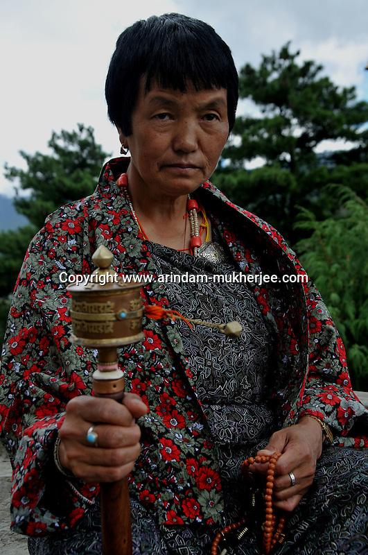 A bhutanese lady with a prayer wheel in her hand. Thimpu. Bhutan. Arindam Mukherjee..