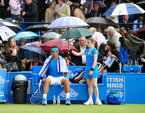 10.06.2011 The AEGON Championships from Queens Club in London. Rafael Nadal of Spain sits in his corner as a ball girl shields him from rain with an umbrella as play is suspended due to rain on day five of the Aegon Championships at the Queen's Club.