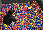 Mimi Ocampo takes a picture of her younger daughter, Meli, in a ball pit at a birthday party for a friend's daughter in London, Ky., on Thursday, Oct. 25, 2012. Ocampo took Meli and her other daughter, Naomi, to the party. Her son, Ozzi, spent the night with his dad, whom Ocampo is separated from. | Photo by Taylor Moak