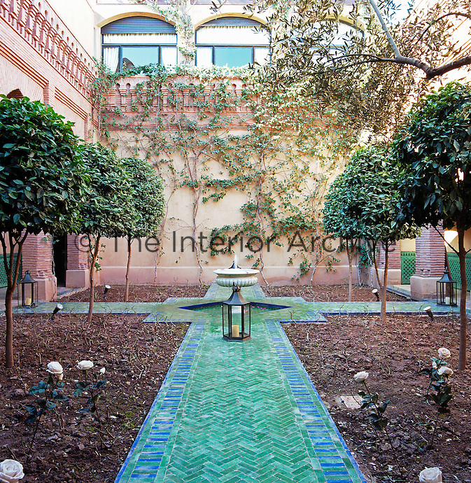 The newly planted flowerbeds in the inner courtyard have a dramatic green tiled walkway and a central fountain