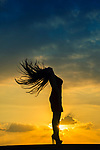 Full length silhouette of a woman flciking hair against a dramatic sunset