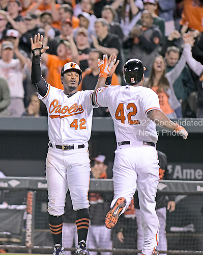 Baltimore Orioles center fielder Adam Jones (10) and Baltimore Orioles designated hitter Delmon Young (27) celebrate their both scoring in the sixth inning against the Baltimore Orioles at Oriole Park at Camden Yards in Baltimore, MD on Wednesday, April 15, 2015.  The Orioles won the game 7 - 5.<br /> Credit: Ron Sachs / CNP<br /> (RESTRICTION: NO New York or New Jersey Newspapers or newspapers within a 75 mile radius of New York City)