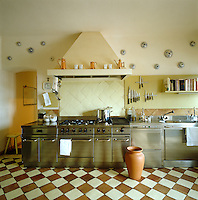 Contemporary stainless steel and traditional terracotta tiles have been seamlessly blended in this kitchen for a warm, rustic yet streamlined and modern workspace