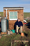 Man sitting in front of his allotment garden shed, Shottisham, Suffolk, England