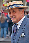 A man in the New York City Easter Parade wearing a gray and purple suit and a flat straw hat with a striped ribbon