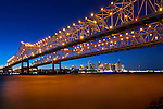 Crescent City Connection Bridges cross over the lower Mississippi River.  The twin cantilever bridges rise over the skyline of New Orleans.