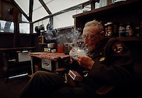 Carl Sharmith, Yosemite National Park's oldest Ranger, lights his pipe in his cabin in Tuolumne Meadows.  Sharsmith's first park service job was as a seasonal ranger-naturalist in 1931.  Besides interpreting for visitors, he did basic research on the alpine meadows of the High Sierra, gathering thousands of herbarium samples and publishing several research papers. His interests included botany, zoology, geology, classical music, Shakespeare, and singing opera.