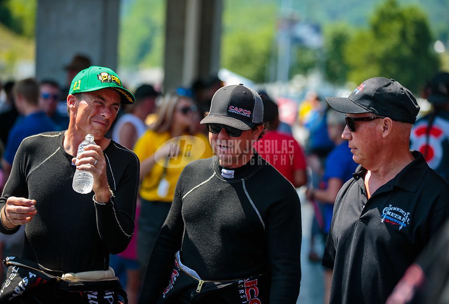 Jun 17, 2018; Bristol, TN, USA; NHRA top fuel driver Clay Millican (left) talks with Steve Torrence (center) and Pat Dakin during the Thunder Valley Nationals at Bristol Dragway. Mandatory Credit: Mark J. Rebilas-USA TODAY Sports