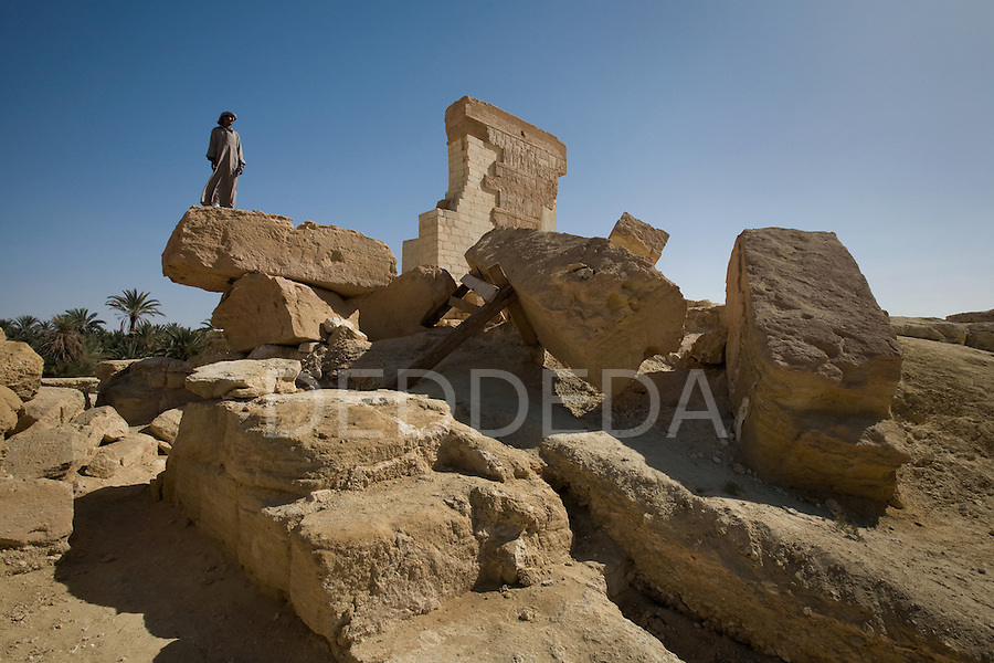 A local Siwan young man stands on the Temple of Umm Ubayd in the Siwa Oasis, which was once attached to the Temple of the Oracle, Egypt.