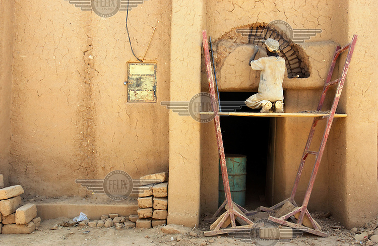 A man builds a decorative archway using a traditional mud brick technique in the old quarter of Agadez.