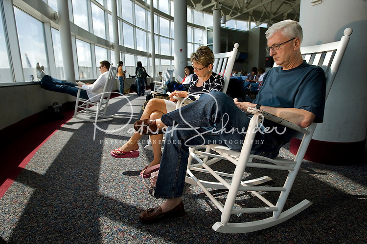 Passengers enjoy Charlotte-Douglas International Airport's famous rocking chairs while waiting for their flights. ..Charlotte-Douglas International Airport, one of US Airways' largest hubs, serves 10 major airlines, including Air Canada, Air Tran, American, Continental, Delta, JetBlue, Lufthansa, Northwest and United. The airport is the nation?s 10th largest in terms of total operations, the 18th largest in terms of total passengers and the 37th largest in terms of cargo. Charlotte-Douglas serves 640 daily flights, including direct flights to 120 cities. ..Photographer has series of images from Charlotte-Douglas International Airport, including aerials. ... PATRICK SCHNEIDER PHOTO.COM
