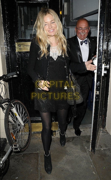 "SIENNA MILLER .Seen leaving after the evening performance of ""Flare Path"", at the Theatre Royal Haymarket, London, England, UK, May 13th 2011..full length black tights dress  ankle boots lace  white long sleeve bag funny .CAP/CAN.©Can Nguyen/Capital Pictures."