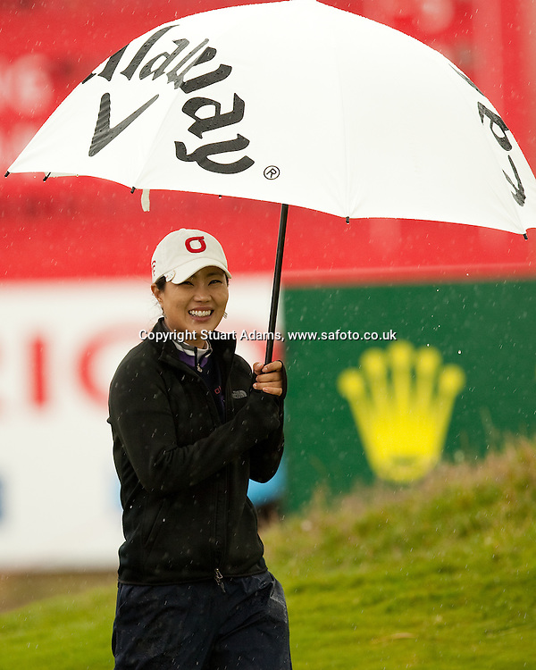 Korea's Meena Lee shelters from the rain during the first round play of the  Ricoh Woman's British Open to be played over the Championship Links from 28th to 31st July 2011; Picture Stuart Adams, SAFOTO. www.safoto.co.uk; 28th July 2011