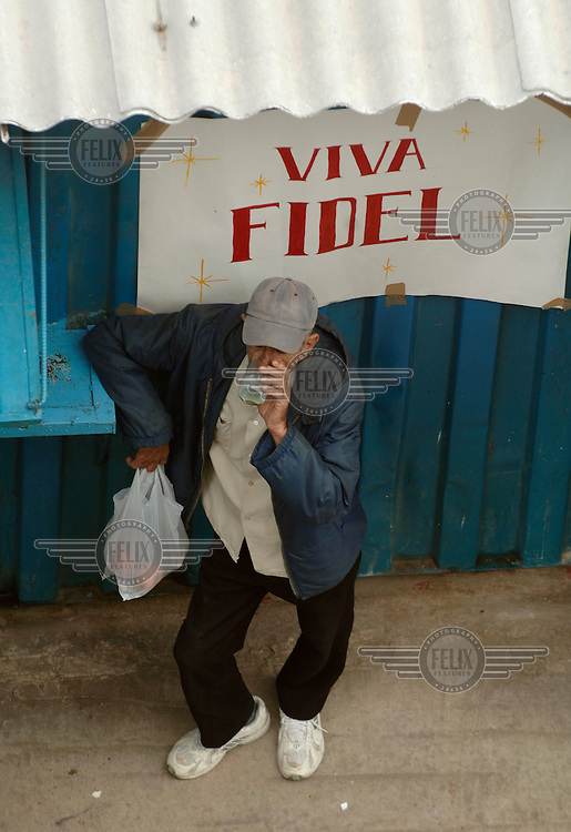 A man drinking a milkshake on a street corner in front of a notice that reads 'Viva Fidel'.