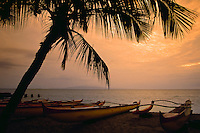 Outrigger canoes on the beach at sunset on Maui in Hawaii