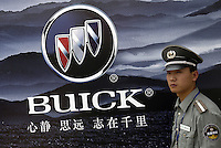 A security guard stands in front of a billboard  of Buick at the Auto China 2004 exhibition in Beijing, China.