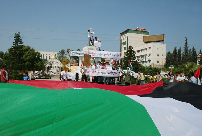 Palestinians carry Palestinian flags during a rally calling for unity between the Gaza Strip and the West bank, in Gaza City. The Israeli Cabinet voted overwhelmingly on Sunday to release 90 Palestinian prisoners in an effort to shore up the moderate Palestinian president, Mahmoud Abbas, in his power struggle with Islamic Hamas militants. But the size of the release disappointed the Palestinians at a time when the two sides are feverishly trying to move peace talks into high gear. The banner on top reads in Arabic: '' We are standing as the olive trees, proud of our past, changing our present and creating our future. ''