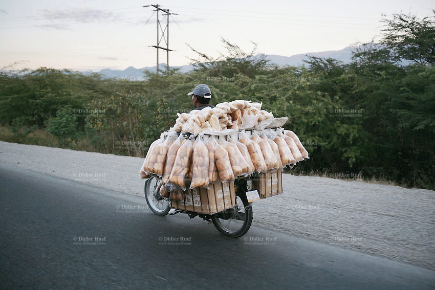 Dominican Republic. San Juan Province. On the road to San Juan de la Maguana. A man rides his motorcycle and carries loafs of breads. © 2006 Didier Ruef