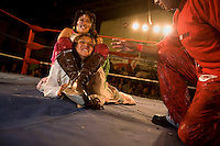 18 year old wrestler Gloria Esperanza (fighting name), Esperanza Gomez (real name) is headlocked by another wrestler during a fight at the Multifuncional building. Esperanza is a Cholita, a wrestler of native Aymara descent. When Cholitas fight they wear traditional costume...