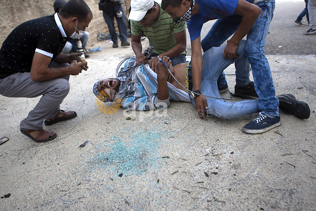 Palestinian protesters help an injured comrade during clashes with Israeli security forces near the Jewish settlement of Bet El, near the West Bank city of Ramallah, on October 14, 2015. Seven Israelis and 30 Palestinians, including children and assailants, have been killed in two weeks of bloodshed in Israel, Jerusalem and the occupied West Bank. The violence has been partly triggered by Palestinians' anger over what they see as increased Jewish encroachment on Jerusalem's Al-Aqsa mosque compound. Photo by Shadi Hatem