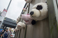 """Banksy enthusiasts flock to the trendy Meatpacking District in New York on Friday, October 11, 2013 to see the eleventh installment of Banksy's art, """"The Sirens of the Lambs"""". This particular sculptural piece consists of a slaughterhouse truck filled with bleating plush animals, controlled by puppeteers, which were driven around by a driver, left,, who remained in character. The elusive street artist is creating works around the city each day, during the month of October accompanied by a satirical recorded message parodying a museum tour which you can get by calling the number 1-800-656-4271 followed by  # and the number of artwork.  (© Richard B. Levine)"""