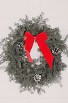 A Christmas wreath hanging on the white front door of a home Red bow