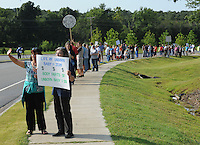 NWA Democrat-Gazette/ANDY SHUPE<br /> Cathy Carter (left) of Rogers and Susan Wagoner of Decatur wave and hold signs Saturday, Aug. 22, 2015, as nearly 200 people gathered to protest in front of the Planned Parenthood office 3729 N Crossover Road in Fayetteville. The protest was a part of a national effort to call for the defunding of the organization.