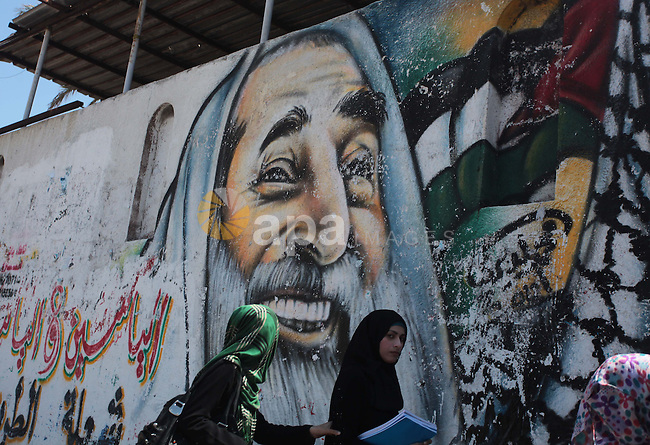 Palestinian University students walk past a mural depicting late Hamas spiritual leader Sheikh Ahmed Yassin, marking the 10th anniversary of his death in Gaza City, March 22, 2014. Photo by Ashraf Amra