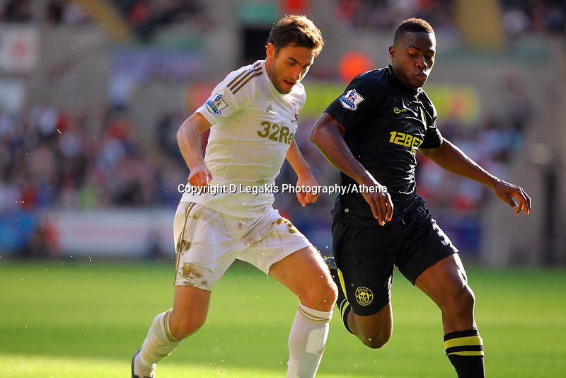 Saturday, 20 October 2012<br /> Pictured L-R: Angel Rangel of Swansea challenged by Maynor Figueroa of Wigan<br /> Re: Barclays Premier League, Swansea City FC v Wigan Athletic at the Liberty Stadium, south Wales.
